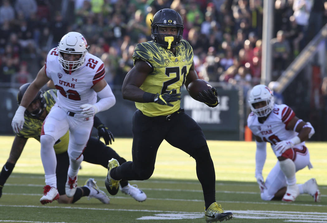 Oregon running back Royce Freeman rushes against Utah's Chase Hansen, left, and Sunia Tauteoli during the second quarter of an NCAA college football game Saturday, Oct. 28, 2017, in Eugene, Ore. ( ...