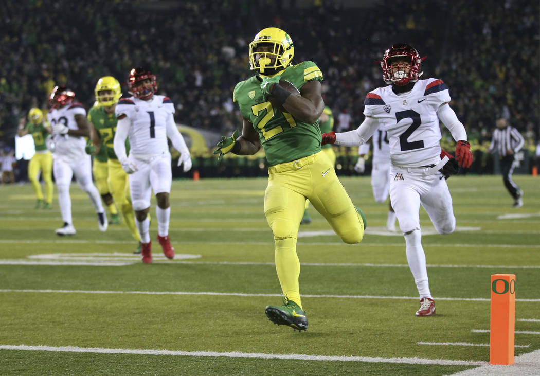 Oregon running back Royce Freeman, center, breaks through the Arizona defense, including Arizona's Lorenzo Burns, right, for a touchdown during the second quarter of an NCAA college football game, ...