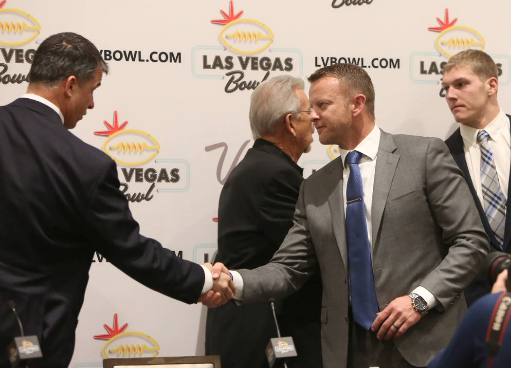 The University of Oregon head coach Mario Cristobal, left, and Boise State head coach Bryan Harsin shake hands after a Las Vegas Bowl press conference at the Hard Rock hotel-casino on Friday, Dec. ...