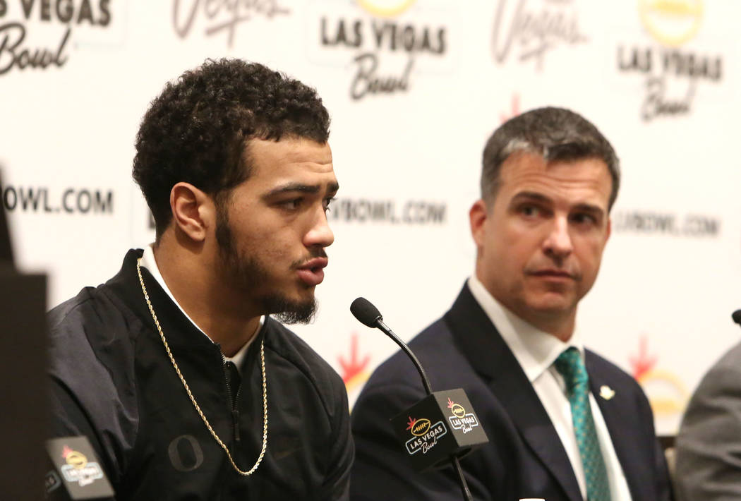 The University of Oregon head coach Mario Cristobal, left, listens as linebacker Troy Dye looks on during a Las Vegas Bowl press conference at the Hard Rock hotel-casino on Friday, Dec. 15, 2017,  ...