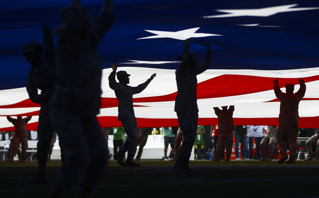 Members of the military are silhouetted while displaying the flag before the start of the Las Vegas Bowl at Sam Boyd Stadium in Las Vegas on Saturday, Dec. 16, 2017. Chase Stevens Las Vegas Review ...