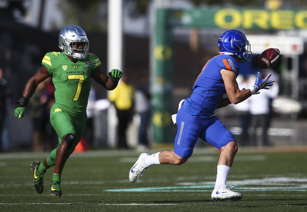Boise State's Sean Modster (8) receives a pass as Oregon's Ugochukwu Amadi (7) runs for the tackle during the Las Vegas Bowl at Sam Boyd Stadium in Las Vegas on Saturday, Dec. 16, 2017. Chase Stev ...