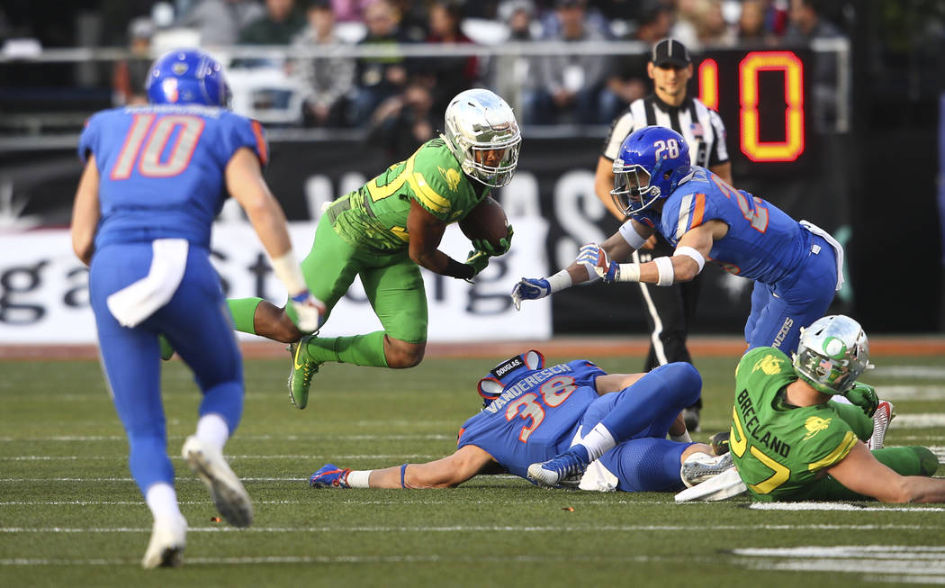 Oregon's Jaylon Redd (30) jumps over Boise State's Leighton Vander Esch (38) while running the ball during the Las Vegas Bowl at Sam Boyd Stadium in Las Vegas on Saturday, Dec. 16, 2017. Chase Ste ...