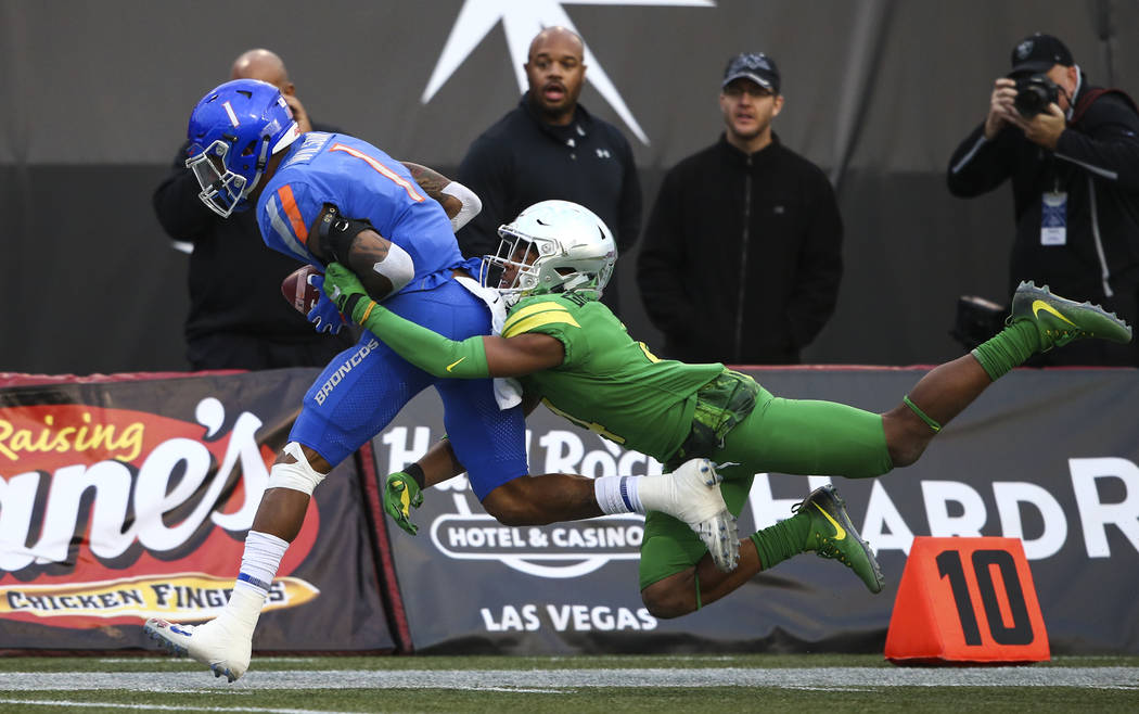 Oregon's Thomas Graham Jr. (4) takes down Boise State's Cedrick Wilson (1) during the Las Vegas Bowl at Sam Boyd Stadium in Las Vegas on Saturday, Dec. 16, 2017. Chase Stevens Las Vegas Review-Jou ...