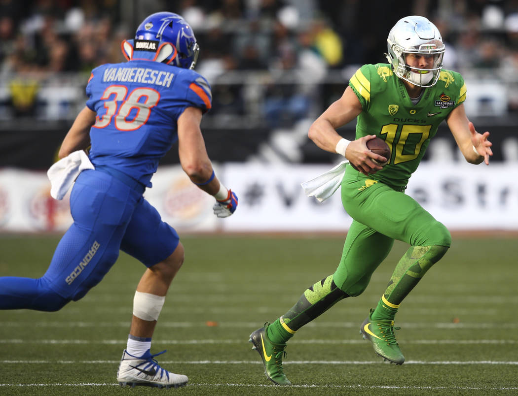 Oregon's Justin Herbert (10) runs the ball past Boise State's Leighton Vander Esch (38) during the Las Vegas Bowl at Sam Boyd Stadium in Las Vegas on Saturday, Dec. 16, 2017. Chase Stevens Las Veg ...