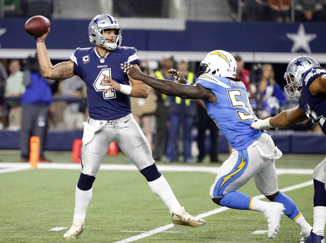 Dallas Cowboys quarterback Dak Prescott (4) throws a pass under pressure from Los Angeles Chargers linebacker Melvin Ingram (54) in the second half of an NFL football game, Thursday, Nov. 23, 2017 ...