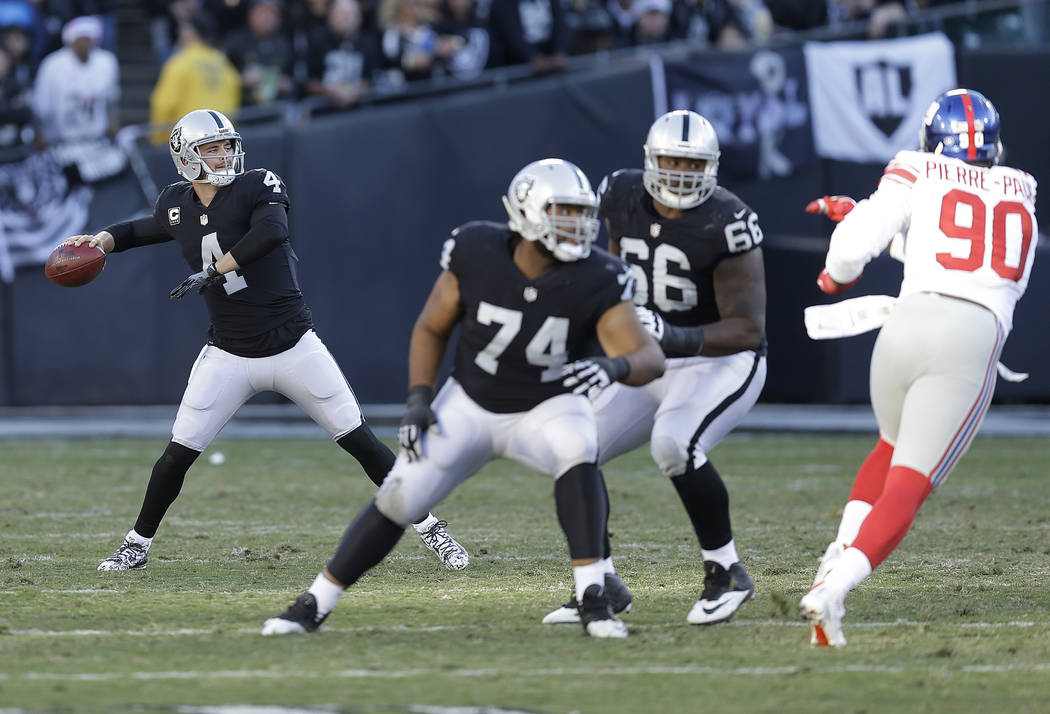 Oakland Raiders quarterback Derek Carr (4) passes against the New York Giants during the second half of an NFL football game in Oakland, Calif., Sunday, Dec. 3, 2017. (AP Photo/Ben Margot)