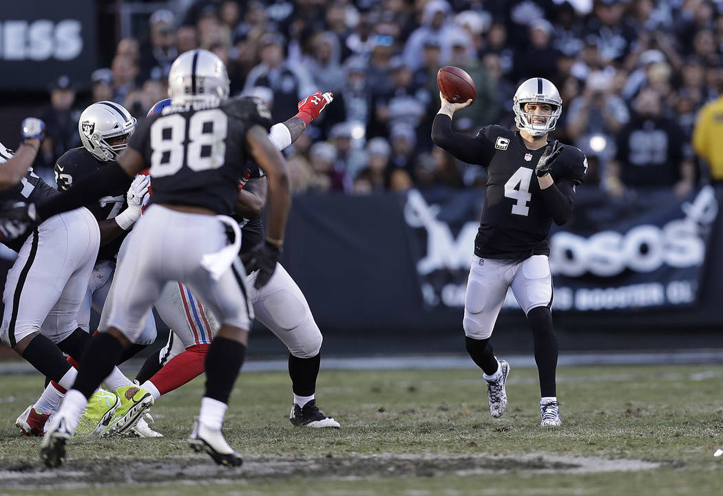 Oakland Raiders quarterback Derek Carr (4) passes against the New York Giants during the second half of an NFL football game in Oakland, Calif., Sunday, Dec. 3, 2017. (AP Photo/Marcio Jose Sanchez)