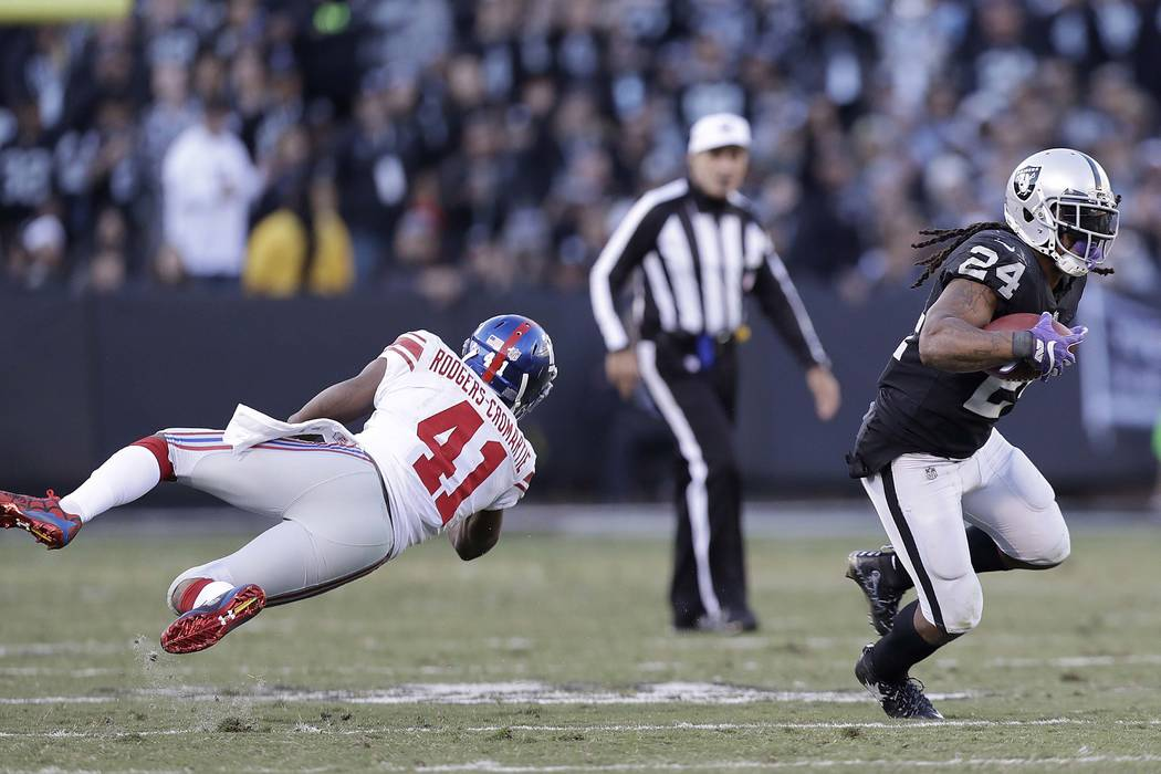 Oakland Raiders running back Marshawn Lynch (24) runs against New York Giants cornerback Dominique Rodgers-Cromartie (41) during the second half of an NFL football game in Oakland, Calif., Sunday, ...