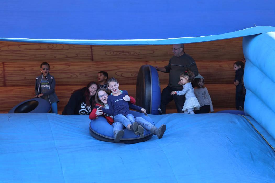 People ride down an inflatable slide duringWinterFestoutside City Hall in Henderson, Saturday, Dec. 9, 2017. Joel Angel Juarez Las Vegas Review-Journal @jajuarezphoto