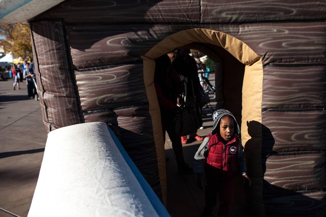Reginald Davis Jr. of Indianapolis, Ind., 4, runs through the entrance of an inflatable slide duringWinterFestoutside City Hall in Henderson, Saturday, Dec. 9, 2017. Joel Angel Juarez  ...