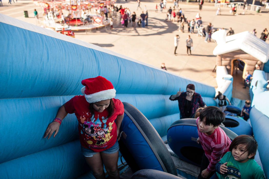 Mia Spencer, 12, left, Caleb Watanabe, 11, center, and Cyrus Spencer, 4, right, all of Whitney, climb up the side of an inflatable slide duringWinterFestoutside City Hall in Henderson, ...