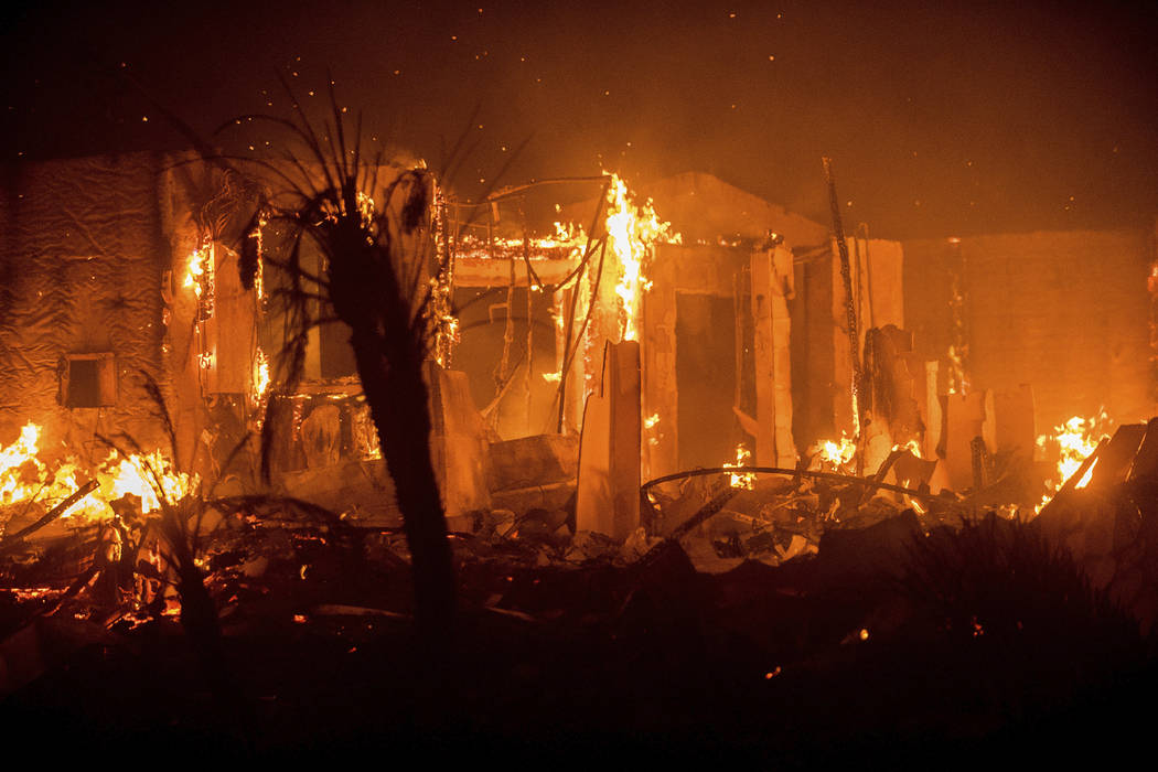 Flames consume a structure as the Lilac fire burns in Bonsai, Calif., on Friday, Dec. 8, 2017. The blaze burned numerous structures and thousands of acres according to fire officials. Wind-swept b ...