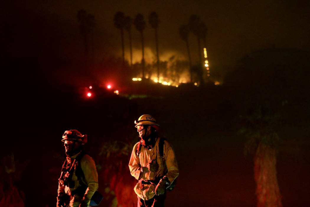 Fire crews look on as they fight a wildfire Thursday, Dec. 7, 2017, in Bonsall, Calif. The wind-swept blazes have forced tens of thousands of evacuations and destroyed dozens of homes in Southern  ...