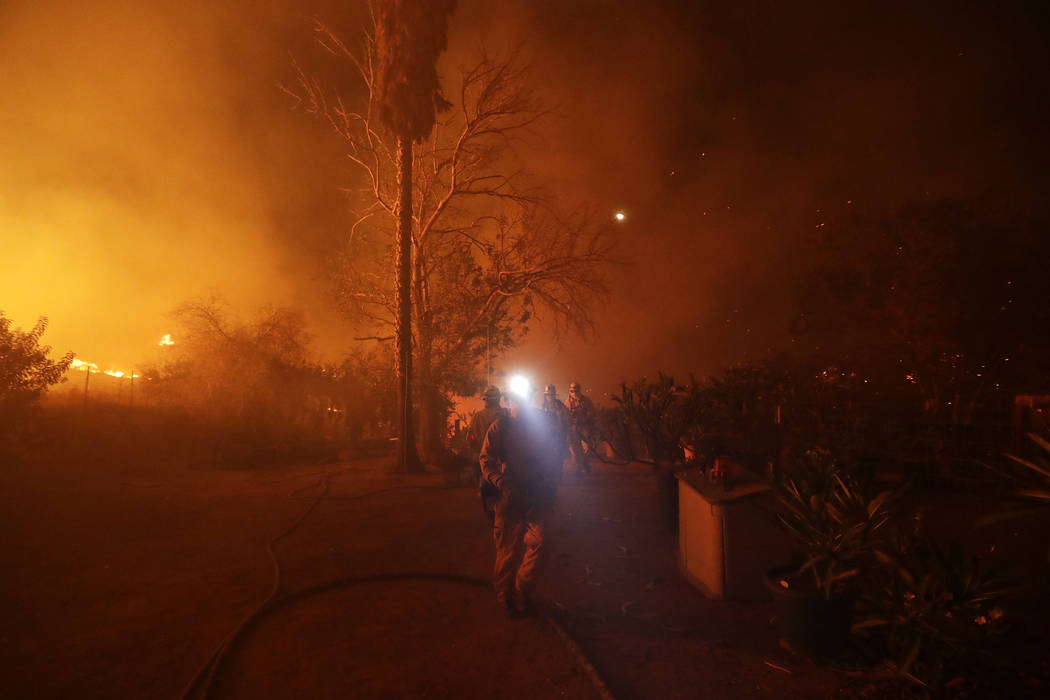 Fire crews prepare to defend a home as a wildfire advances Thursday, Dec. 7, 2017, in Bonsall, Calif. The wind-swept blazes have forced tens of thousands of evacuations and destroyed dozens of hom ...