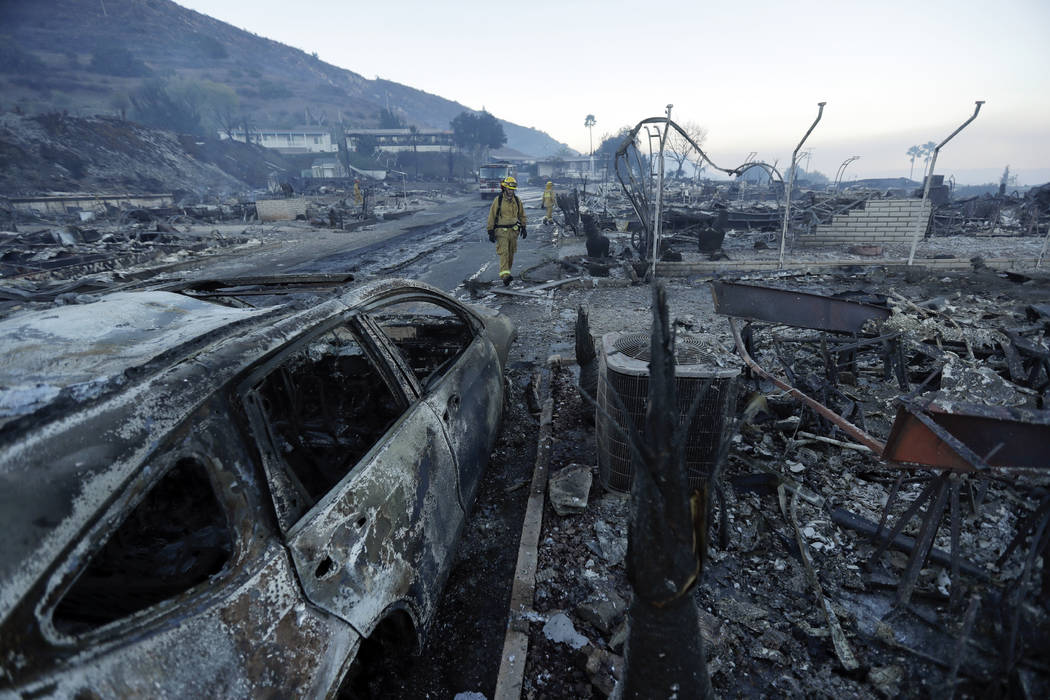 Fire crews search for hot spots among destroyed homes in the Rancho Monserate Country Club community Friday, Dec. 8, 2017, in Fallbrook, Calif. The wind-swept blazes have forced tens of thousands  ...
