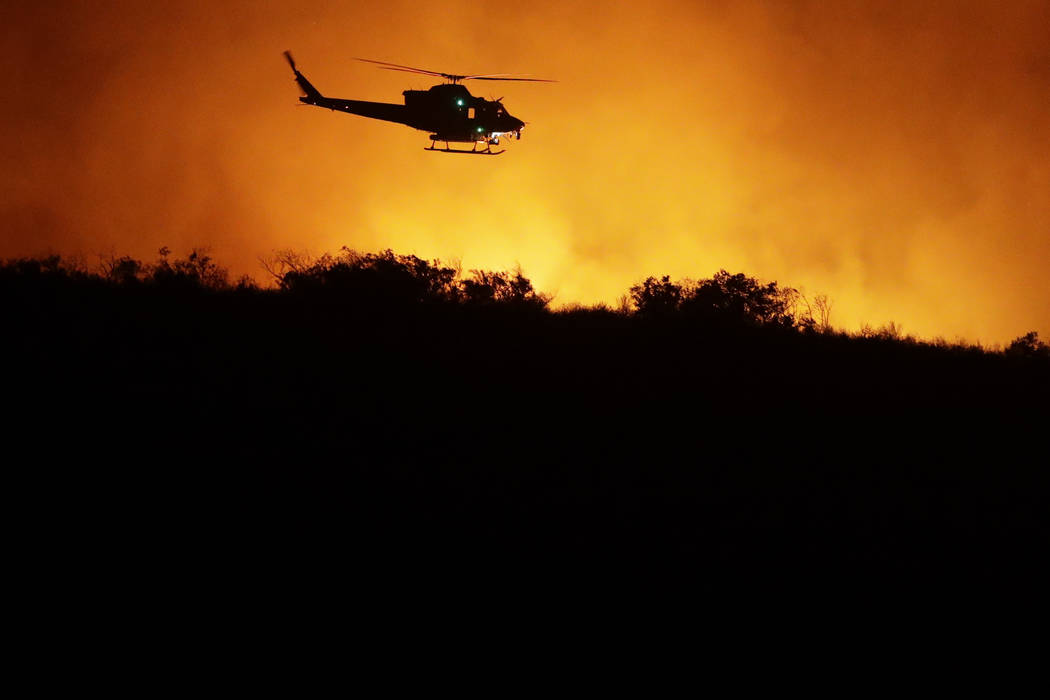 A helicopter flies over a wildfire Thursday, Dec. 7, 2017, in Bonsall, Calif. The wind-swept blazes have forced tens of thousands of evacuations and destroyed dozens of homes in Southern Californi ...
