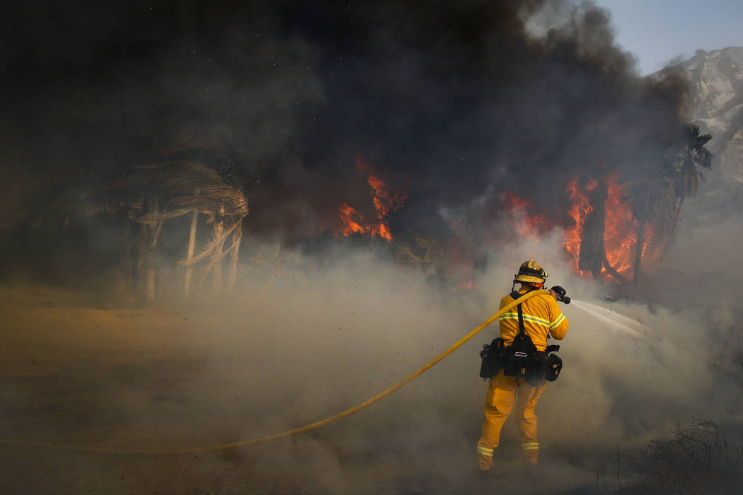 A firefighter battles a wildfire at Faria State Beach in Ventura, Calif., Thursday, Dec. 7, 2017. The wind-swept blazes have forced tens of thousands of evacuations and destroyed dozens of homes.  ...