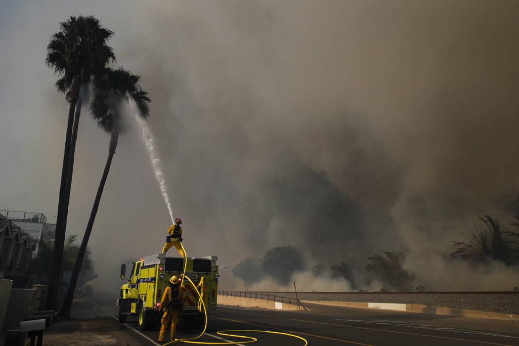 Firefighters battle a wildfire as smoke rises from burning palm trees at Faria State Beach in Ventura, Calif., Thursday, Dec. 7, 2017. The wind-swept blazes have forced tens of thousands of evacua ...