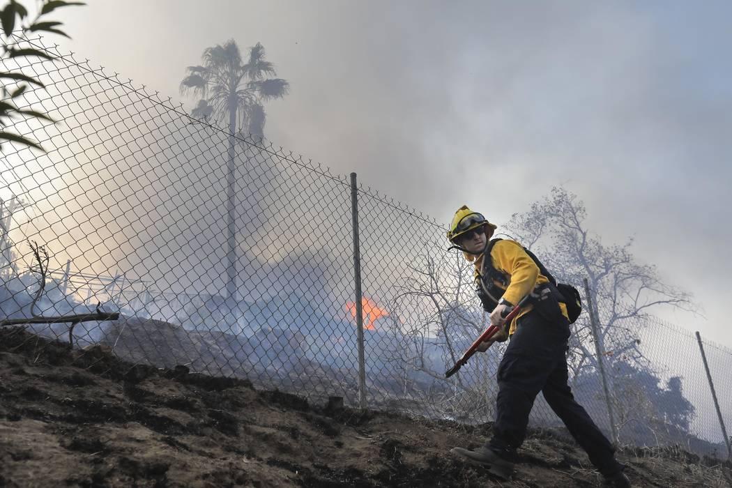 A Vista firefighter cuts a hole in a fence at a home on West Lilac Road in Bonsall, Calif., Thursday, Dec, 7, 2017.  The biggest and most destructive of the windblown fires raking Southern Califor ...