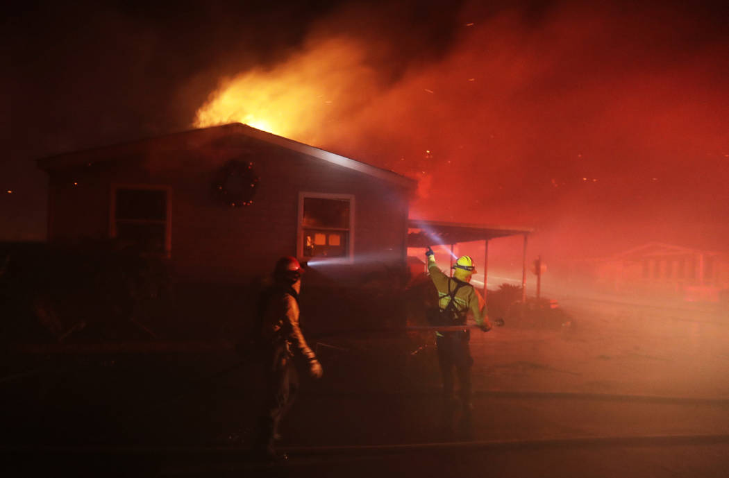 Fire crews work among burning homes at the Rancho Monserate Country Club community Thursday, Dec. 7, 2017, in Fallbrook, Calif. The wind-swept blazes have forced tens of thousands of evacuations a ...