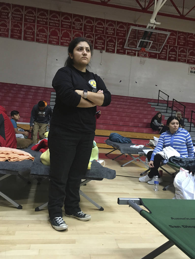 Cynthia Olvera listens to an announcement that the evacuation shelter she's in at Fallbrook High School in Fallbrook, Calif., is itself being evacuated because of the wildfire in San Diego  ...