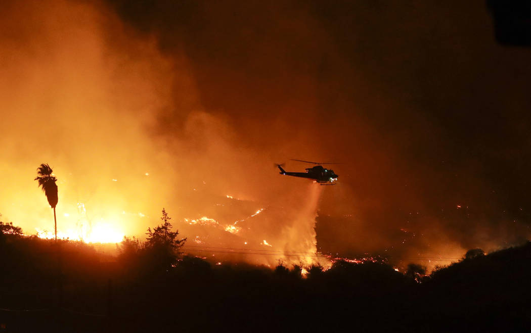 A helicopter drops water over a wildfire Thursday, Dec. 7, 2017, in Bonsall, Calif. The wind-swept blazes have forced tens of thousands of evacuations and destroyed dozens of homes in Southern Cal ...
