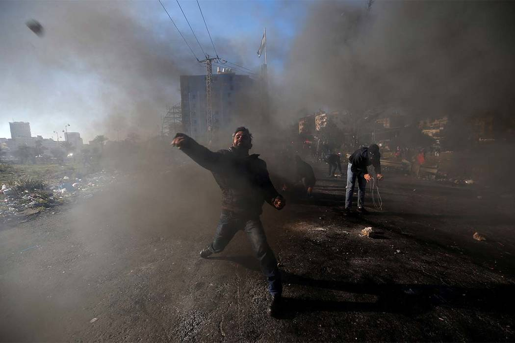 """A Palestinian protester hurls stones toward Israeli troops during clashes as Palestinians call for a """"Day of Rage"""" in response to President Donald Trump's recognition of Jerusalem as Israel's capi ..."""