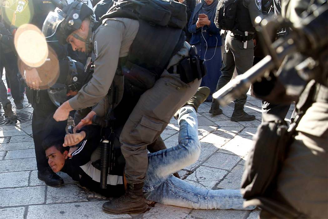 """Israeli border policemen detain a Palestinian man during scuffles at Damascus Gate after Friday prayers in Jerusalem's Old City, as Palestinians call for a """"day of rage"""" in response to U.S. Presid ..."""