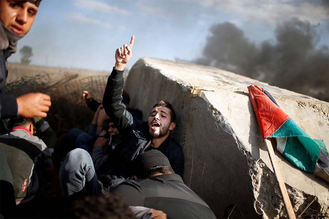 """A Palestinian protester gestures as he takes cover during clashes with Israeli troops  as Palestinians call for a """"Day of Rage"""" in response to President Donald Trump's recognition of Jerusalem as  ..."""