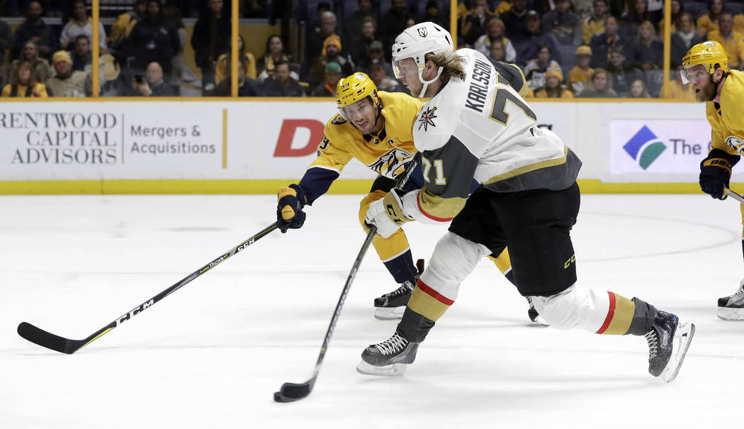 Vegas Golden Knights center William Karlsson (71), of Sweden, shoots as he Nashville Predators' Roman Josi (59), of Switzerland, defends during the first period of an NHL hockey game Friday, Dec.  ...