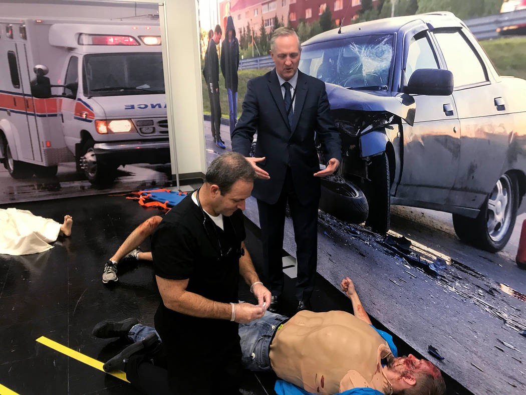 RJ Dietrick (right), wears a surgical suit as Dr. Derek Meeks, an assistant professor at Touro University in Henderson, demonstrates how to treat a patient with a lung injury at the scene of a sim ...