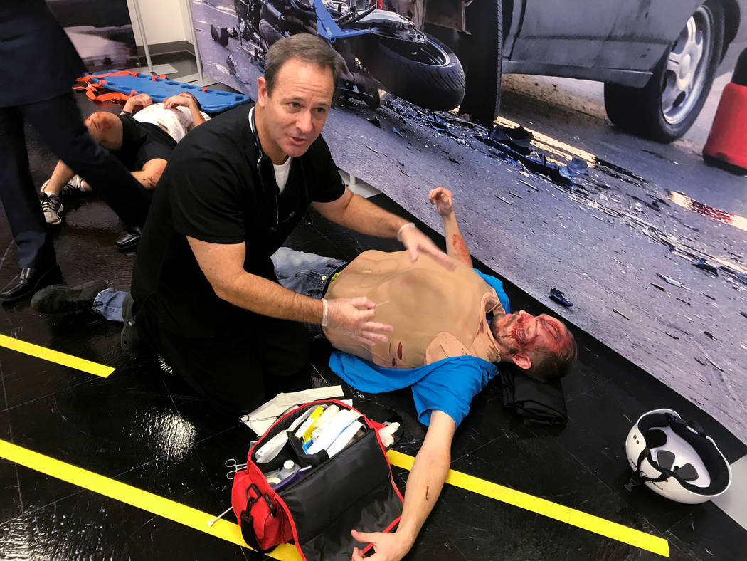 RJ Dietrick, right, wears a surgical suit as Dr. Derek Meeks, an assistant professor at Touro University in Henderson, demonstrates how to treat a patient with a lung injury at the scene of a simu ...