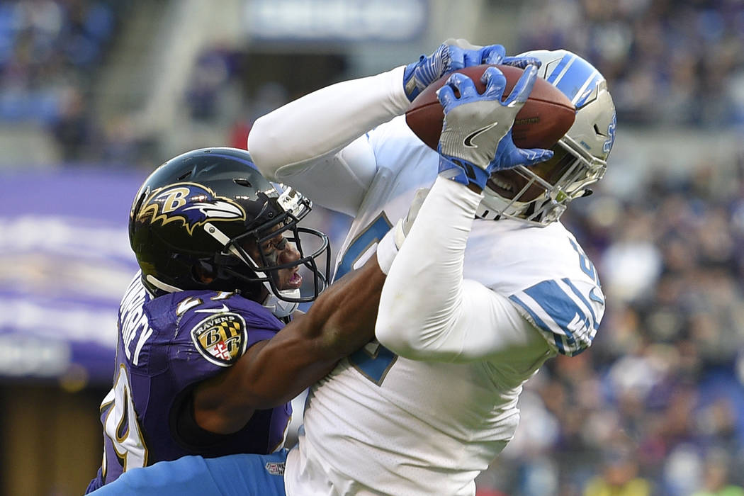 Detroit Lions tight end Michael Roberts, right, catches a pass as he is pressured by Baltimore Ravens defensive back Marlon Humphrey in the second half of an NFL football game, Sunday, Dec. 3, 201 ...