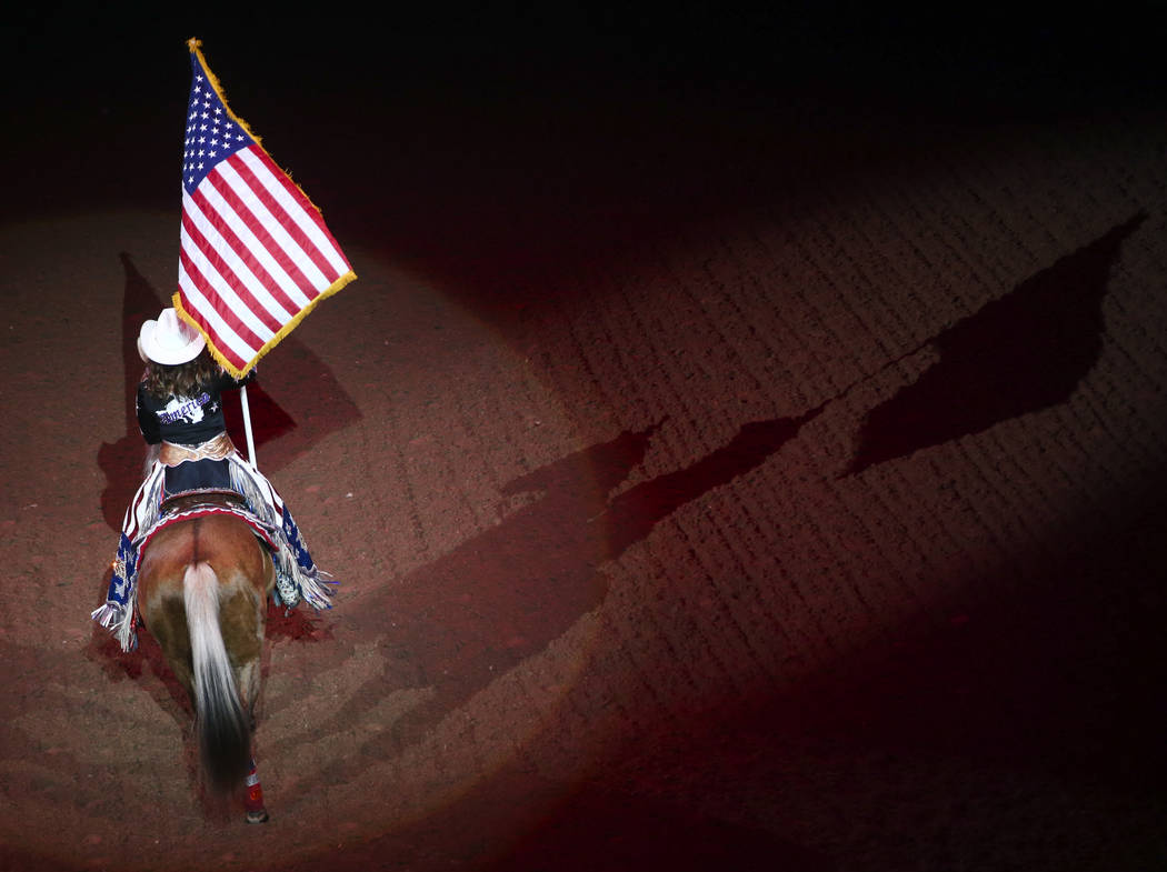 The American flag is presented during the opening ceremony on the first night of the National Finals Rodeo at the Thomas & Mack Center in Las Vegas on Thursday, Dec. 7, 2017. Chase Stevens Las ...