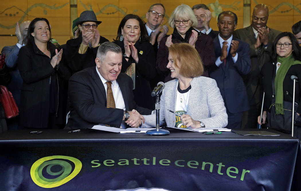 Seattle Mayor Jenny Durkan, right, shakes hands with Los Angeles-based Oak View Group CEO Tim Leiweke after they signed an agreement to renovate KeyArena, Wednesday, Dec. 6, 2017, in Seattle. Durk ...