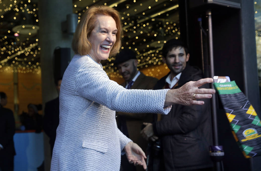 Seattle Mayor Jenny Durkan playfully tosses a pair of Seattle SuperSonics socks to a reporter during her remarks before signing an agreement to renovate KeyArena, Wednesday, Dec. 6, 2017, in Seatt ...