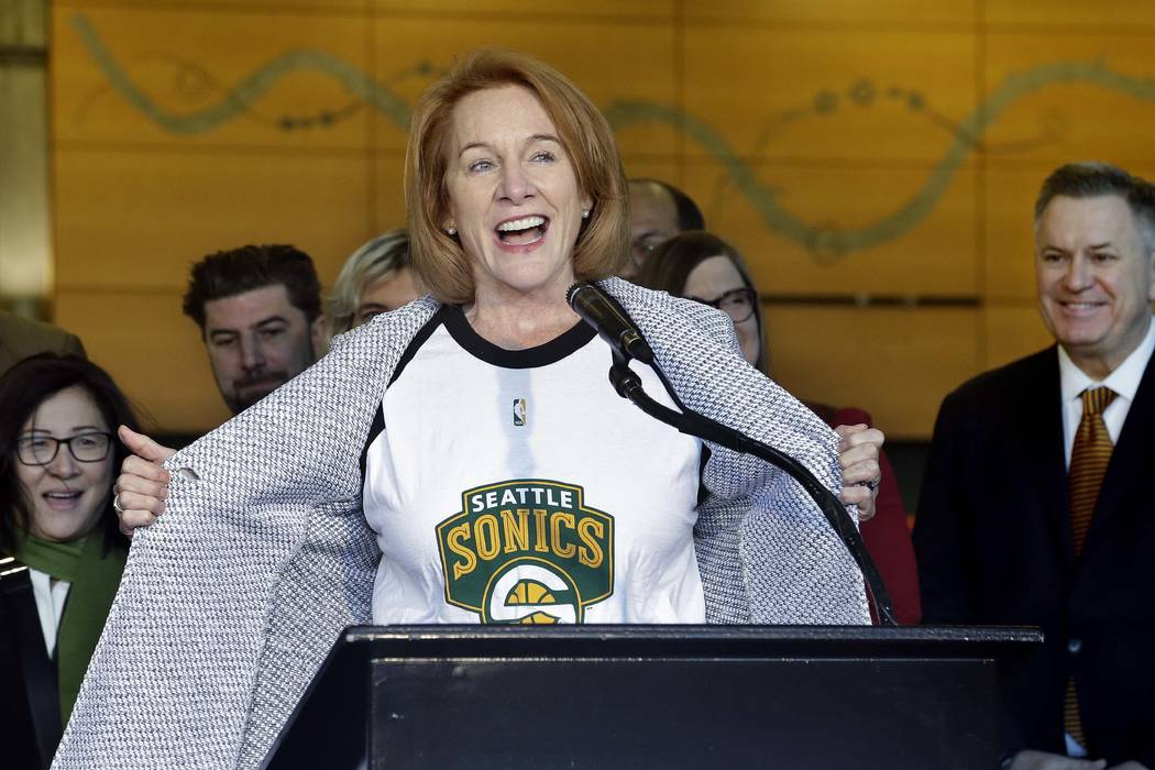 Seattle Mayor Jenny Durkan pulls back her jacket to reveal a Seattle SuperSonics T-shirt as she speaks before signing an agreement to renovate KeyArena, Wednesday, Dec. 6, 2017, in Seattle. Durkan ...