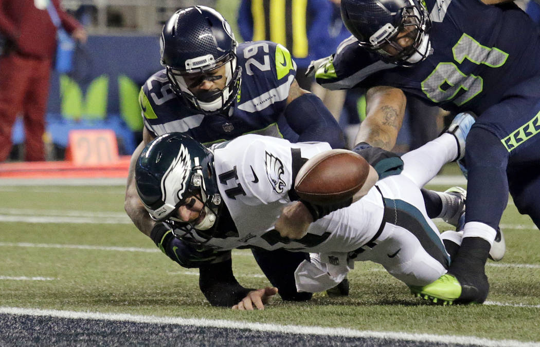 Philadelphia Eagles quarterback Carson Wentz (11) fumbles the ball near the goal line and into the end zone as Seattle Seahawks' Earl Thomas (29) and Sheldon Richardson (91) move in during the sec ...