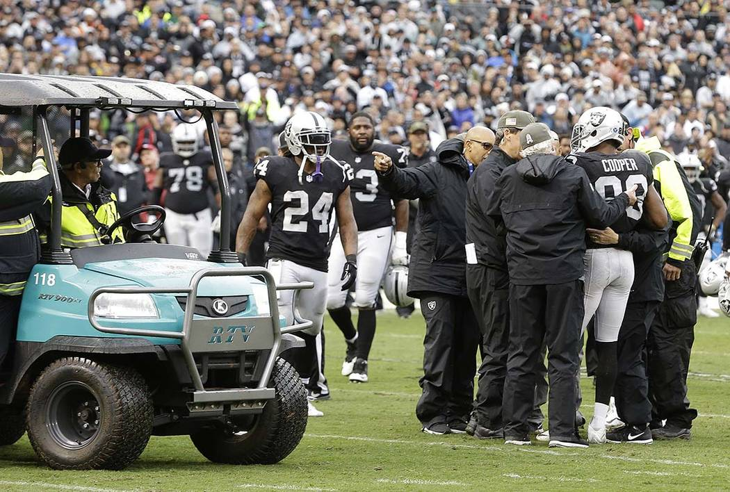 Oakland Raiders wide receiver Amari Cooper (89) is tended to by trainers during the first half of an NFL football game against the Denver Broncos in Oakland, Calif., Sunday, Nov. 26, 2017. (AP Pho ...