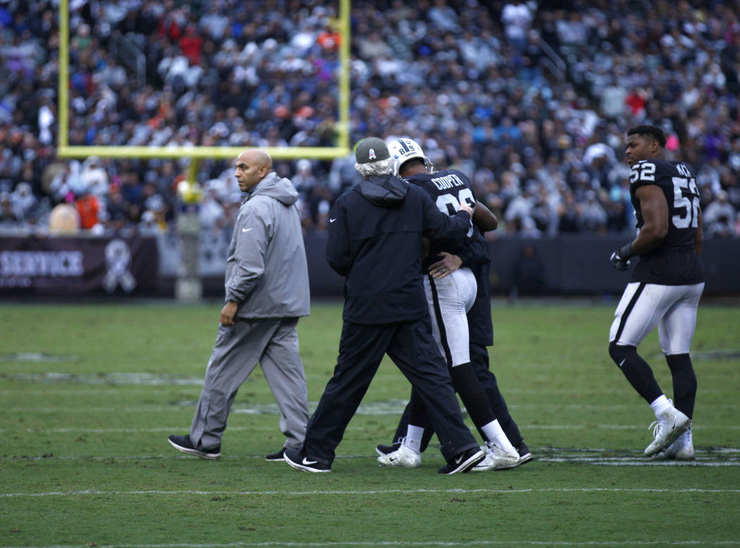 Oakland Raiders wide receiver Amari Cooper (89) is taken off the field by trainers after being knocked unconscious during the first half of a NFL game against the Denver Broncos in Oakland, Calif. ...