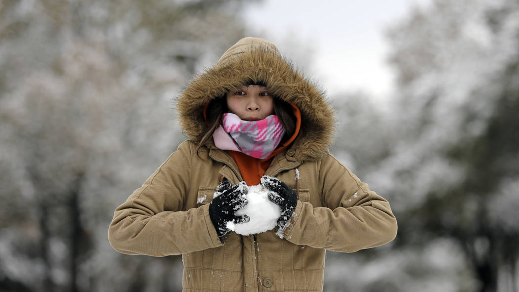 Christine Co makes a snowball while playing in the snow Friday, Dec. 8, 2017, in Spring, Texas, north of Houston. Rare snowfall in many parts of southern Texas has knocked out power to thousands,  ...