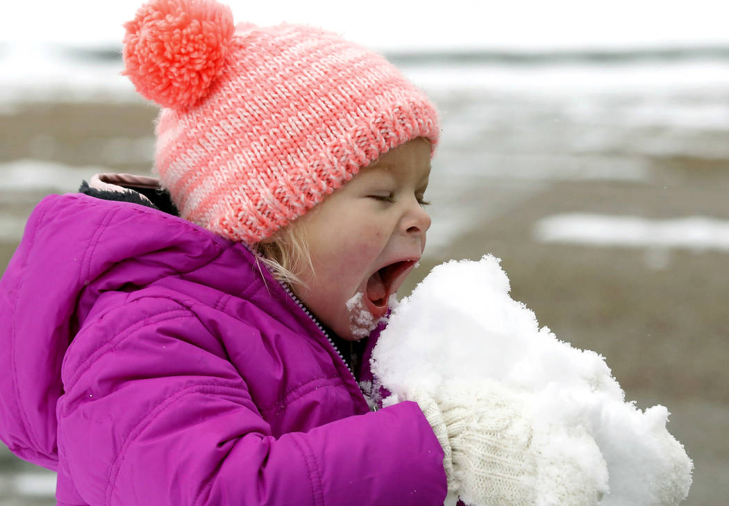 Emmaline Dendinger enjoys a hearty bite of snow in her mid-Jackson, Miss., neighborhood, Friday, Dec. 8, 2017. (AP Photo/Rogelio V. Solis)
