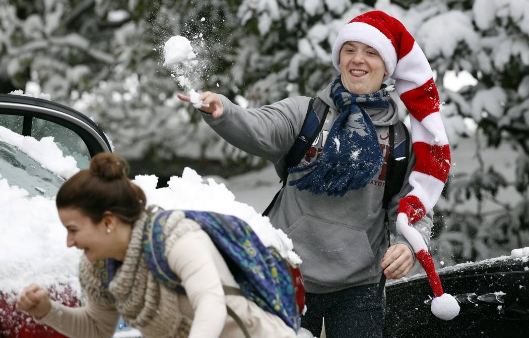 A Belhaven University student throws a snowball at a school mate as students blow off some final exam anxiety with a series of campus wide snowball fights Friday, Dec. 8, 2017, in Jackson, Miss. ( ...