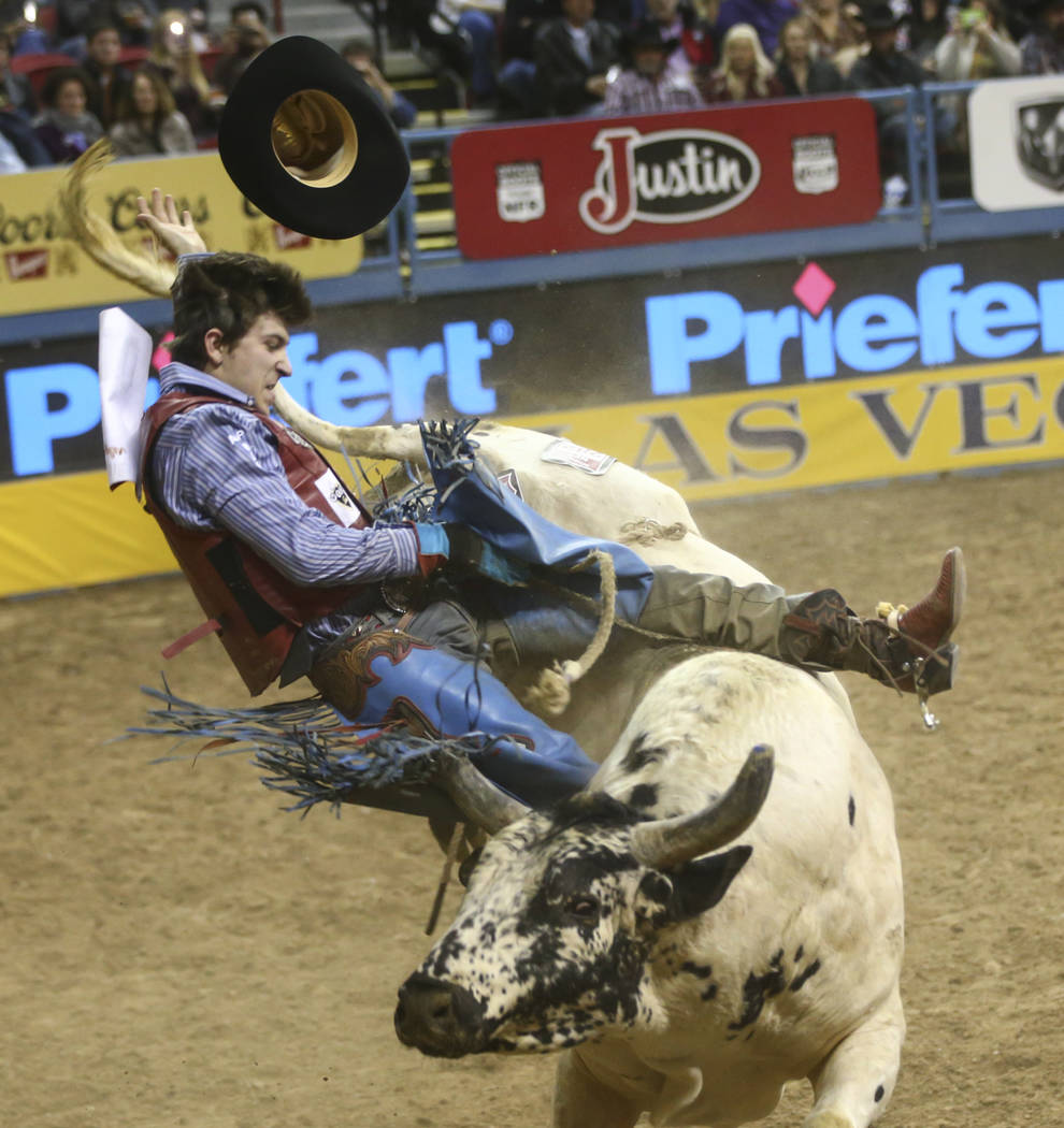 Roscoe Jarboe gets bucked off by Bull Butler while competing in the bull riding event during the second night of the National Finals Rodeo at the Thomas & Mack Center in Las Vegas on Friday, D ...