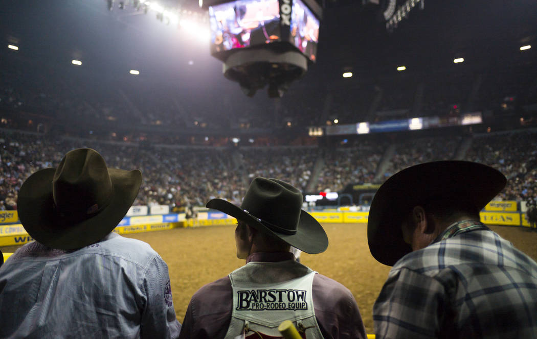 Contestants and officials watch competitors in the bareback riding event during the second night of the National Finals Rodeo at the Thomas & Mack Center in Las Vegas on Friday, Dec. 8, 2017.  ...