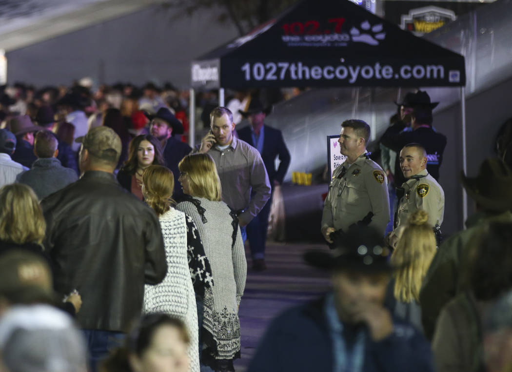 Las Vegas police keep an eye on the crowd as attendees make their way in for the second night of the National Finals Rodeo at the Thomas & Mack Center in Las Vegas on Friday, Dec. 8, 2017. Cha ...