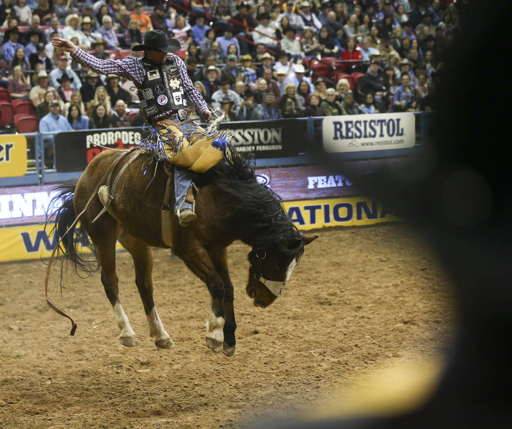 Taos Muncy competes in the saddle bronc riding event during the second night of the National Finals Rodeo at the Thomas & Mack Center in Las Vegas on Friday, Dec. 8, 2017. Chase Stevens Las Ve ...