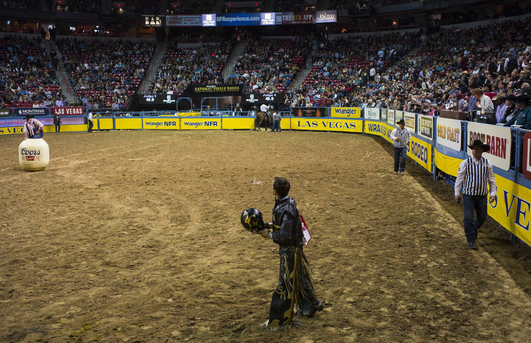 Sage Kimzey checks his score after competing in the bull riding event during the second night of the National Finals Rodeo at the Thomas & Mack Center in Las Vegas on Friday, Dec. 8, 2017. Cha ...