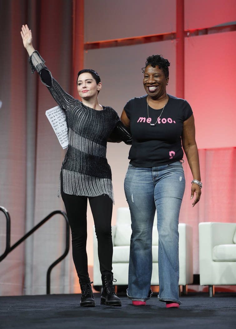 Actress Rose McGowan, left, waves after being introduced by Tarana Burke, right, founder, #MeToo Campaign, at the inaugural Women's Convention in Detroit, Friday, Oct. 27, 2017. McGowan recently w ...